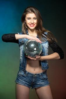 Retrato de uma jovem mulher atraente com bola de espelhos.
