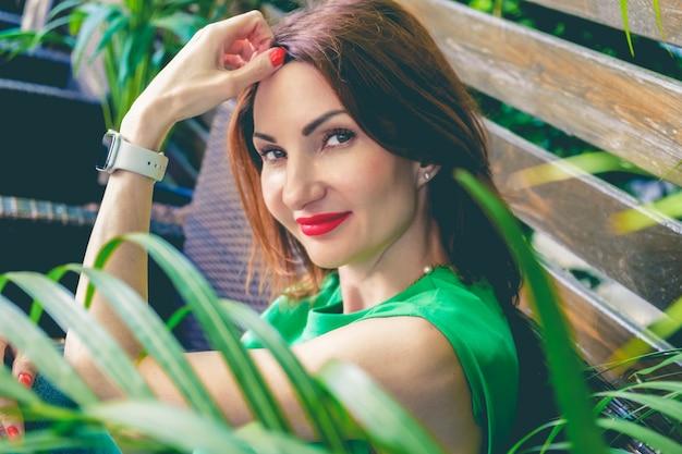 Retrato de uma jovem mulher atraente, com cabelo ruivo e lábios vermelhos brilhantes, na blusa de manga curta verde. mulher está sentada em um banco de madeira entre plantas verdes e sorrindo.