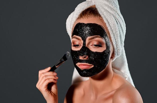 Retrato de uma jovem mulher atraente com uma toalha na cabeça, aplicando uma máscara de limpeza preta com um pincel no rosto em uma parede cinza.