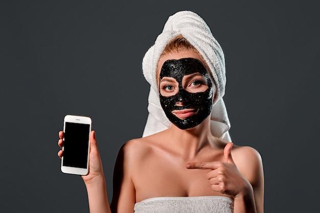 Retrato de uma jovem mulher atraente com uma toalha na cabeça com uma máscara de limpeza preta no rosto com um telefone em uma parede cinza.