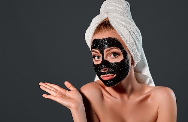 Retrato de uma jovem mulher atraente com uma toalha na cabeça com uma máscara de limpeza preta no rosto em uma parede cinza.