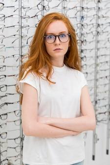 Retrato de uma jovem mulher atraente, de pé na loja de óptica, com o braço cruzado