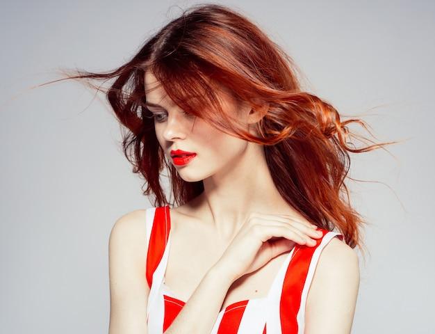 Retrato de uma jovem mulher atraente e bonita com lábios vermelhos, cabelo vermelho a voar