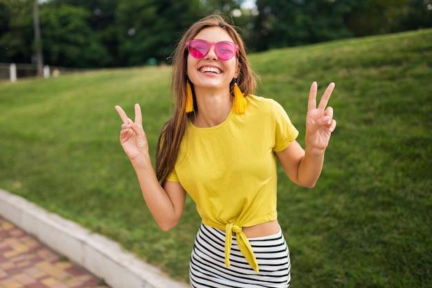 Retrato de uma jovem mulher atraente e elegante, posando no parque da cidade, sorrindo, alegre, positiva, vestindo blusa amarela, minissaia listrada, bolsa, óculos de sol rosa, tendência da moda no estilo de verão