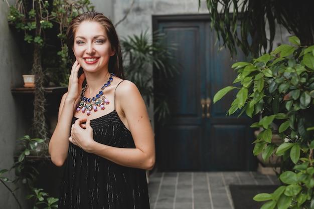 Retrato de uma jovem mulher atraente em um elegante vestido preto posando em uma vila tropical, sexy, elegante estilo verão, acessórios de colar da moda, sorrindo, joias, pele natural pura do rosto
