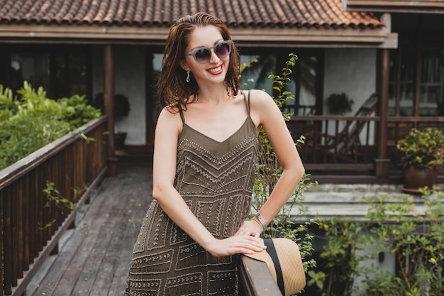 Retrato de uma jovem mulher atraente em um vestido elegante, chapéu de palha, estilo de verão, tendência da moda, férias, sorrindo, acessórios elegantes, óculos de sol, posando em villa tropical em bali