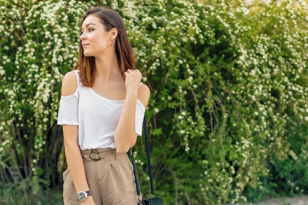 Retrato de uma jovem mulher atraente em uma rua em um dia ensolarado