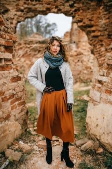 Retrato de uma jovem mulher atraente entre paredes de tijolo.