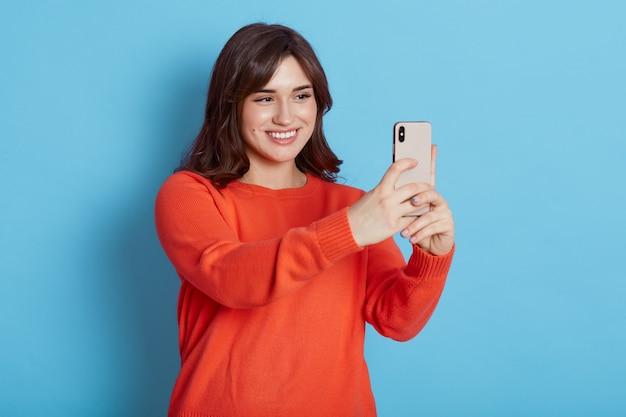 Retrato de uma jovem mulher atraente, fazendo selfie foto com telefone inteligente isolado sobre a parede azul, senhora olha para o dispositivo com um sorriso feliz, mulher de cabelos escuros tem chamada de vídeo.