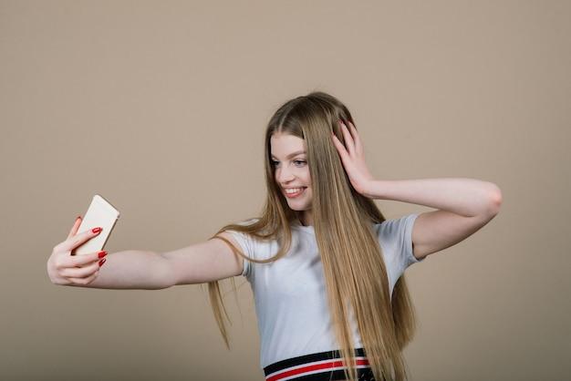Retrato de uma jovem mulher atraente fazendo selfie foto em smartphone isolada em um fundo branco