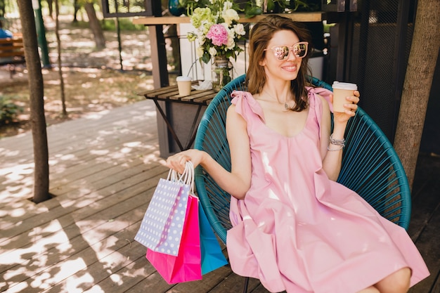 Retrato de uma jovem mulher atraente feliz sorridente, sentado no café com sacos de compras, bebendo café, roupa de moda verão, vestido de algodão rosa, vestuário da moda