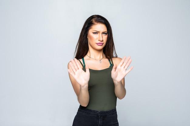Retrato de uma jovem mulher atraente, mostrando o sinal de stop com palm isolado