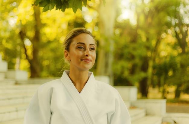 Retrato de uma jovem mulher atraente no quimono branco. mulher esporte ao ar livre. artes marciais