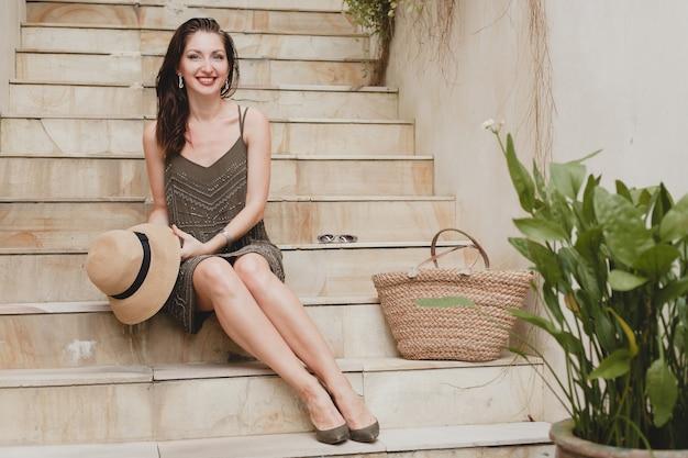 Retrato de uma jovem mulher atraente sentada na escada com um vestido elegante, segurando um chapéu de palha, estilo de verão, tendência da moda, férias, sorrindo, pernas finas, acessórios elegantes, bolsa