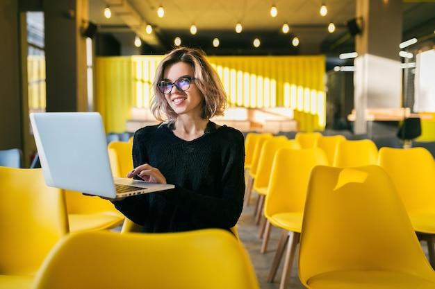 Retrato de uma jovem mulher atraente sentada na sala de aula, trabalhando no laptop de óculos, o aluno aprendendo na sala de aula com muitas cadeiras amarelas