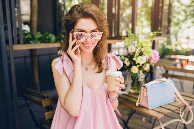 Retrato de uma jovem mulher atraente sentada num café, roupa de moda de verão, estilo hippie, vestido rosa de algodão, óculos de sol, sorrindo, bebendo café, acessórios elegantes, roupas da moda, falando ao telefone