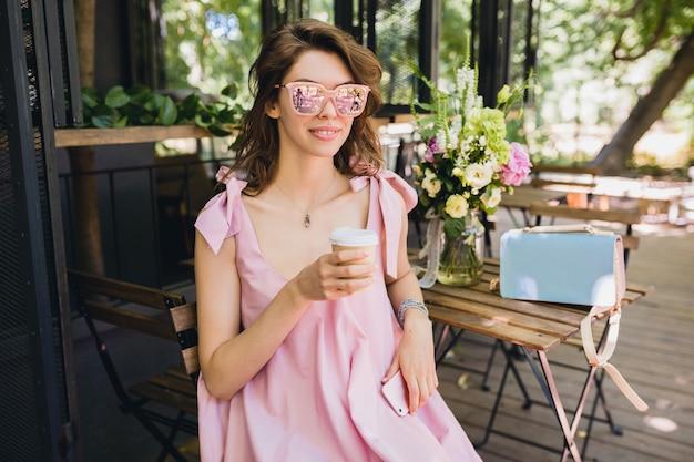 Retrato de uma jovem mulher atraente, sentado no café com roupa de moda de verão, vestido de algodão rosa, óculos de sol, sorrindo, bebendo café, acessórios elegantes, relaxante, vestuário da moda