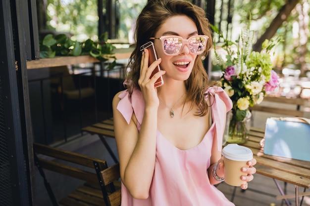 Retrato de uma jovem mulher atraente, sentado no café, roupa de moda de verão, vestido de algodão rosa, óculos de sol, sorrindo, bebendo café, acessórios elegantes, roupas da moda, falando no telefone