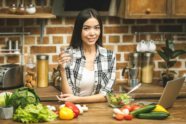 Retrato de uma jovem mulher bebendo água na cozinha em casa
