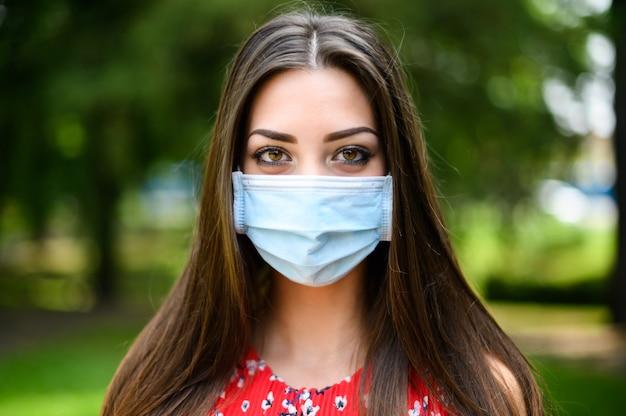Retrato de uma jovem mulher bonita ao ar livre em um parque usando uma máscara durante os tempos de coronavírus