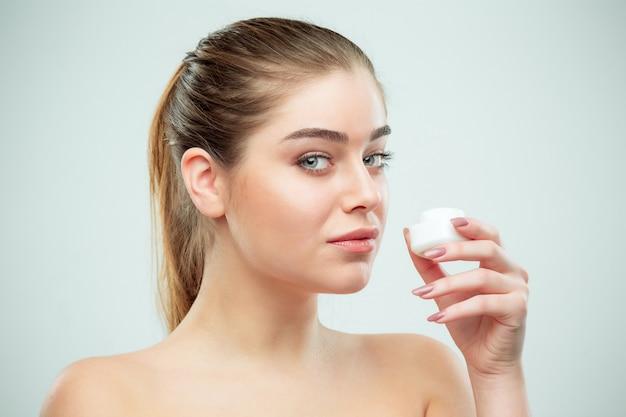 Retrato de uma jovem mulher bonita, aplicar creme hidratante no rosto