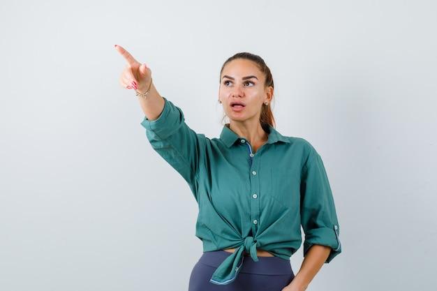 Retrato de uma jovem mulher bonita apontando para longe em uma camisa verde e olhando a vista frontal confusa