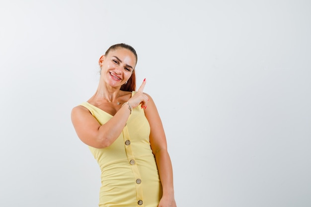 Retrato de uma jovem mulher bonita apontando para o canto superior direito do vestido e olhando para a frente alegre