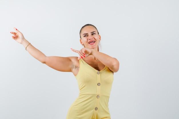 Retrato de uma jovem mulher bonita apontando para o canto superior esquerdo do vestido e olhando para a frente alegre