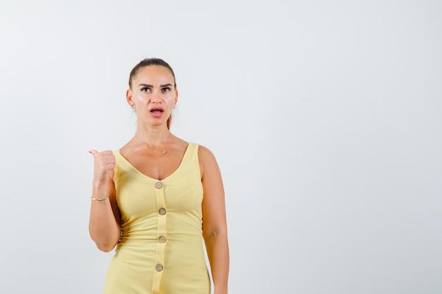 Retrato de uma jovem mulher bonita apontando para trás com o polegar no vestido e olhando perplexa para a frente