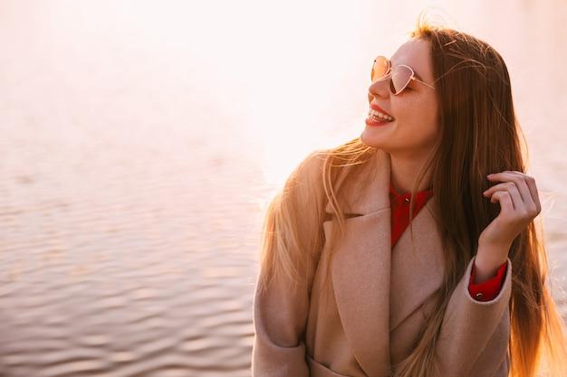 Retrato de uma jovem mulher bonita, apreciando o pôr do sol no lago. cores quentes do sol.