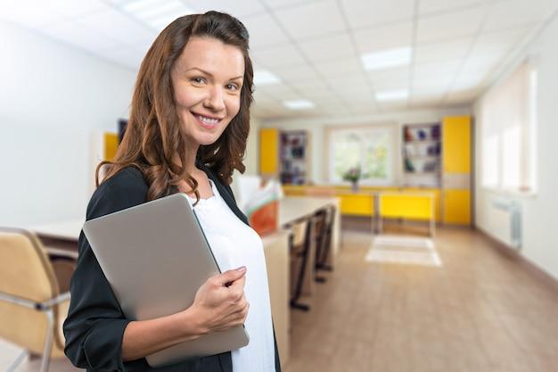 Retrato de uma jovem mulher bonita brunnete segurando laptop