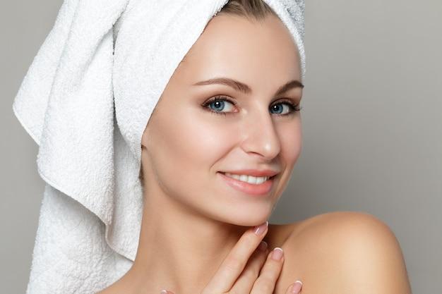 Retrato de uma jovem mulher bonita caucasiana tocando seu rosto isolado sobre fundo branco.