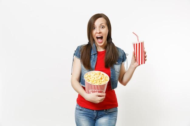 Retrato de uma jovem mulher bonita chocada em roupas casuais, assistindo a um filme de cinema, segurando um balde de pipoca e um copo plástico de refrigerante ou coca-cola isolado no fundo branco. emoções no conceito de cinema.