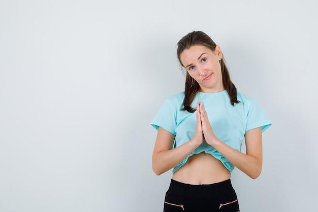 Retrato de uma jovem mulher bonita com as mãos em um gesto de oração em t-shirt, calças e olhando pensativo com vista frontal