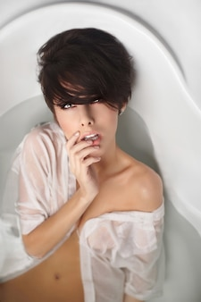 Retrato de uma jovem mulher bonita com cabelo curto, desfrutando de banho em camisa de homem branco tocando os lábios
