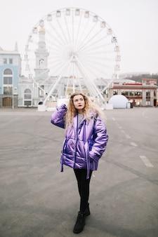 Retrato de uma jovem mulher bonita com cabelo loiro encaracolado ao ar livre. beleza, conceito de moda. estilo de rua. bokeh de fundo