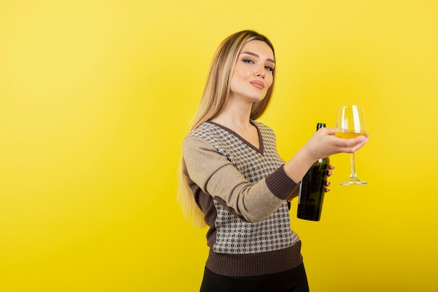 Retrato de uma jovem mulher bonita com copo de vinho branco posando.