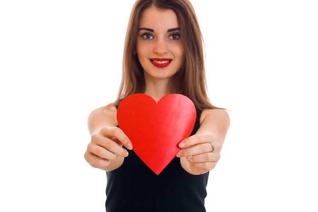 Retrato de uma jovem mulher bonita com coração vermelho isolado na parede branca