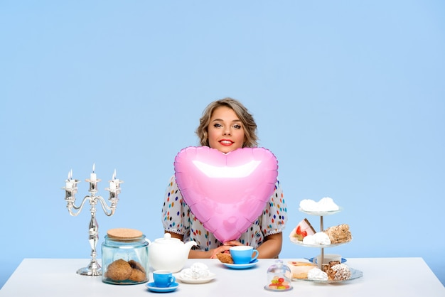 Retrato de uma jovem mulher bonita com doces sobre parede azul