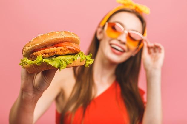 Retrato de uma jovem mulher bonita com fome comendo hambúrguer