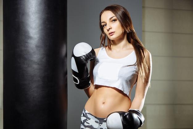 Retrato de uma jovem mulher bonita com luvas de boxe no ginásio.