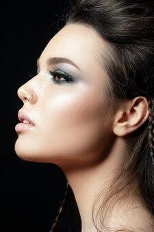 Retrato de uma jovem mulher bonita com maquiagem de noite. modelo posando sobre fundo preto. olhos esfumados prateados.