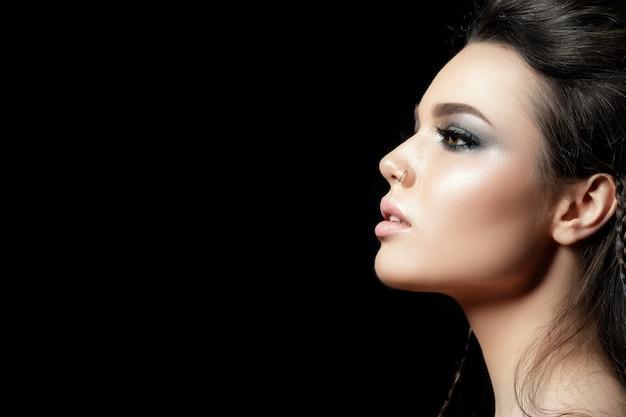 Retrato de uma jovem mulher bonita com maquiagem de noite. modelo posando sobre fundo preto.