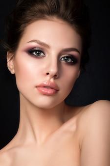 Retrato de uma jovem mulher bonita com maquiagem de noite posando sobre fundo preto
