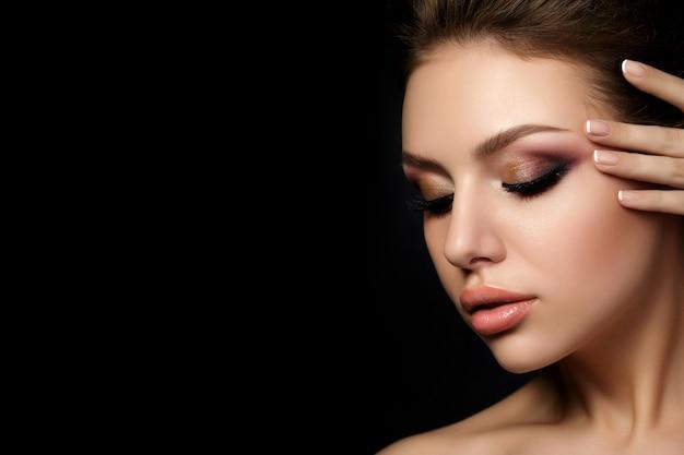 Retrato de uma jovem mulher bonita com maquiagem de noite tocando seu rosto sobre um fundo preto