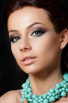 Retrato de uma jovem mulher bonita com maquiagem de noite usando colar azul