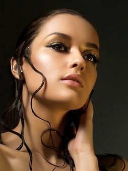 Retrato de uma jovem mulher bonita com maquiagem dourada moda e cabelo molhado. beleza.