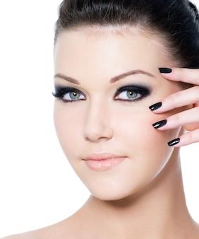 Retrato de uma jovem mulher bonita com maquiagem preta e manicure.
