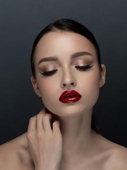 Retrato de uma jovem mulher bonita com noite maquiagem tocando seu rosto. maquiagem