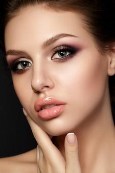 Retrato de uma jovem mulher bonita com noite maquiagem tocando seu rosto sobre o fundo preto.